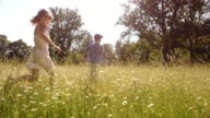 SLO MO Boy and girl running across summer meadow video