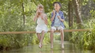 SLO MO A young boy and a girl sitting on a footbridge blowing bubbles video
