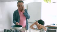 Young boy and his grandfather cooking together video