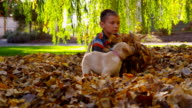 Young boy and puppy playing in fall leaves, slow motion video