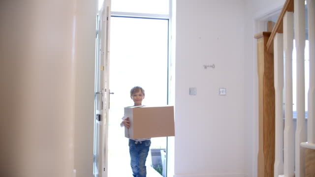Young Boy Carrying Box Into New Home On Moving Day video