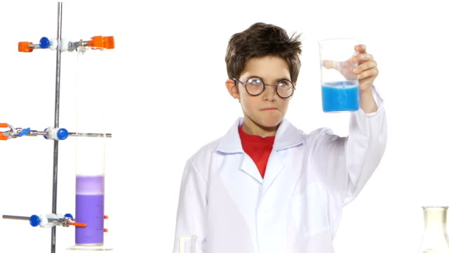 Young boy chemist wearing uniform, red shirt and round glasses in  laboratory making some experiment and evaluates on white background video