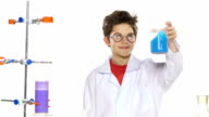 Young boy chemist wearing uniform, red shirt and round glasses in  laboratory making some experiment and wonders on white background video