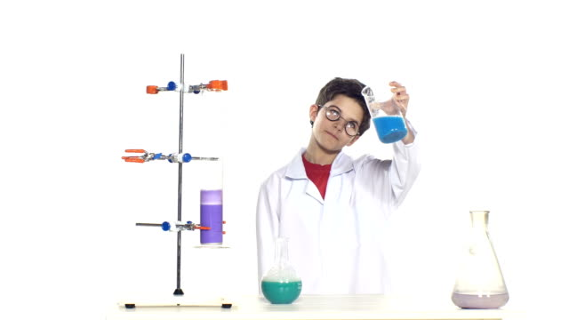 Young boy chemist wearing uniform, red shirt and round glasses in laboratory making some experiment and evaluates, standing by the table, on white background video