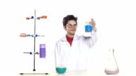 Young boy chemist wearing uniform, red shirt and round glasses in laboratory making some experiment and evaluates, standing by the table, on white background, slow motion video