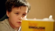 Young boy concentrating on reading a book video