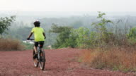 Young boy cycling in a hilly trail video