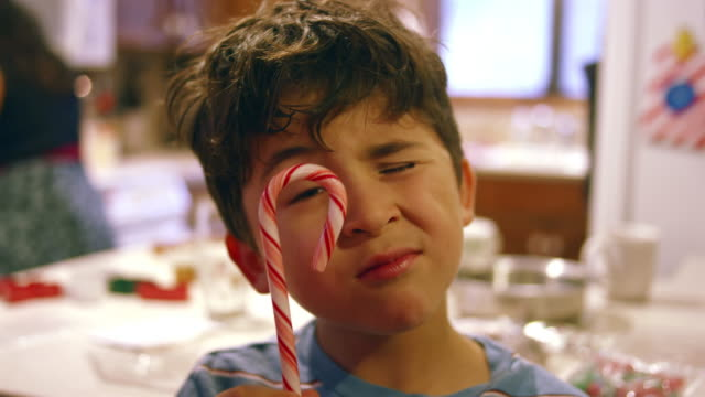 Young boy eating a candy cane in the kitchen video