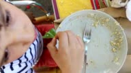 Young boy eating. Child finishing plate. Kid eating seen from above. 90 degree angle. Overhead view video