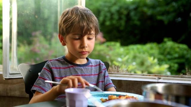 Young boy eating lunch / supper. 8 year old kid eating video