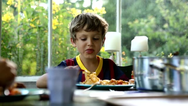 Young boy eating lunch. supper. 8 year old kid eating video