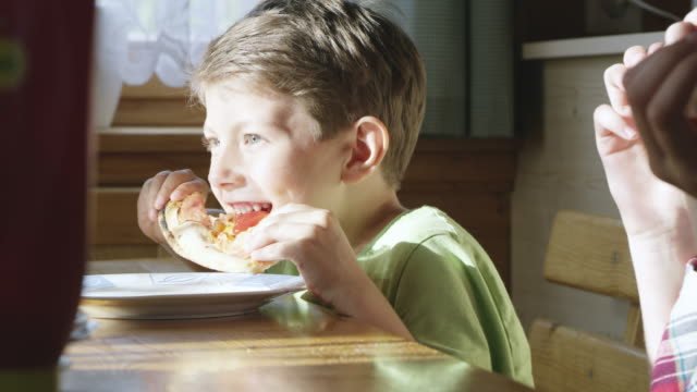 MS Young boy eating slice of pizza at the table video
