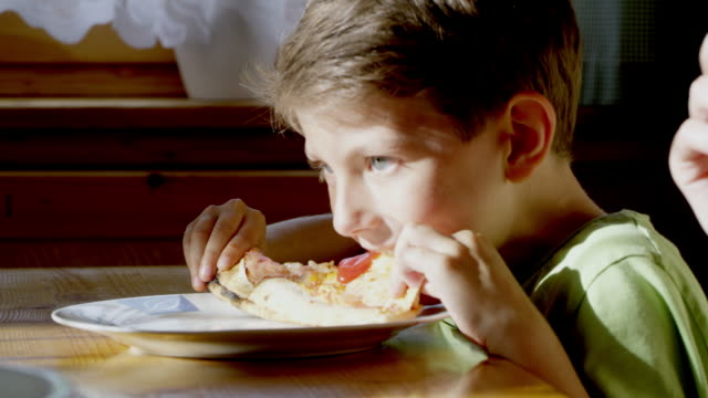 MS Young boy eating slice of pizza video