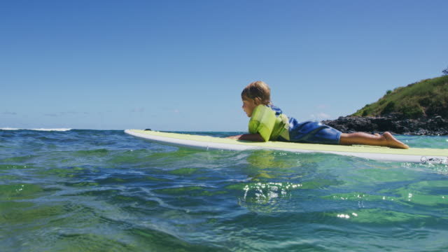 Young boy floating on surfboard video