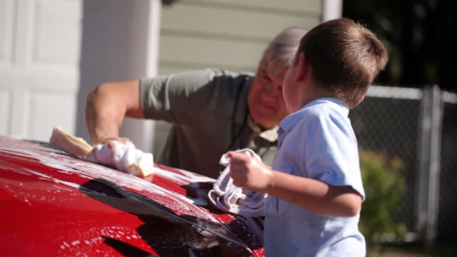 Young boy helps Grandfather wash car video