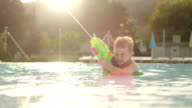 SLOW MOTION CLOSE UP: Young boy in shallow pool aiming and shooting with fun water gun in aqua park at beautiful golden sunset video
