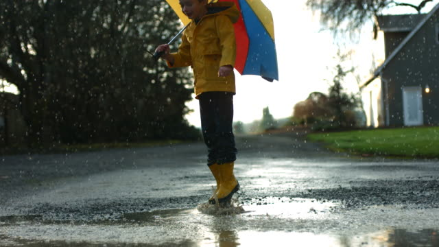 Young boy jumping in puddles with umbrella, slow motion video