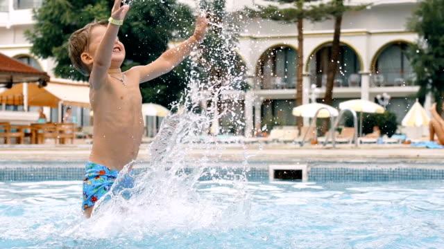 Young boy kid child splashing in swimming pool having fun leisure activity. video