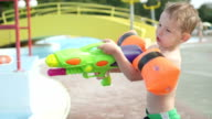 SLOW MOTION CLOSE UP: Young boy kid having a water fight, shooting his father and he gets splashed back in sunny summer in fun water park video