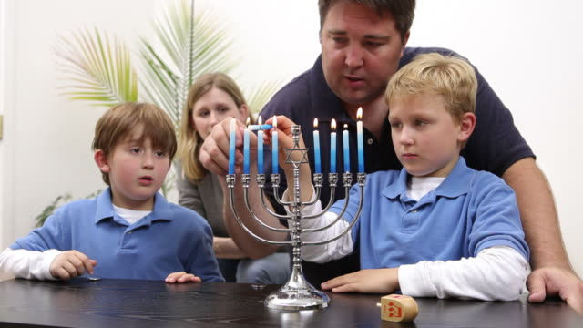 Young boy lights candles on menorah video