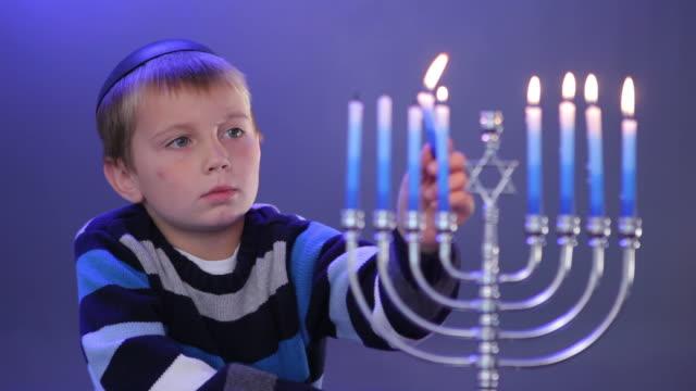Young boy lights menorah video