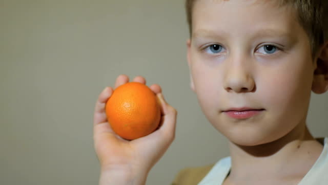 Young boy looking happy at camera and keep a mandarin. Slow motion. video