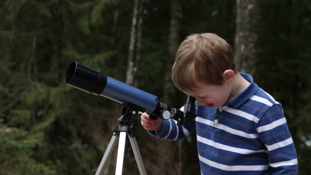 Young boy looking through telescope video