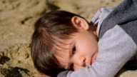 Young Boy Lying on Sand video