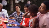 Young boy on dad's knee at family barbecue flexing muscle video