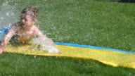 Young boy on water slide, slow motion video