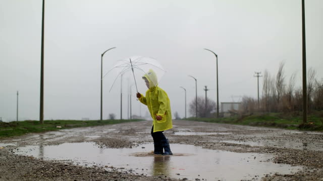 A young boy outside in the rain video