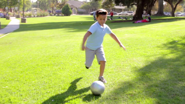 Young Boy Playing Football In Park video