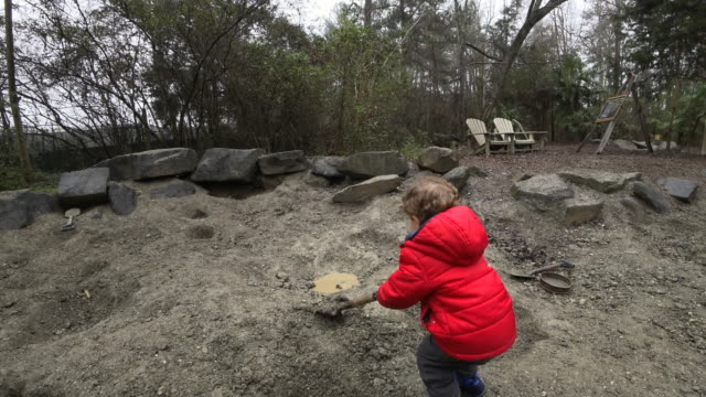 Young boy playing in a muddy sand pit video