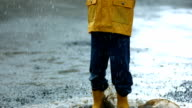 Young boy playing in rain, slow motion video