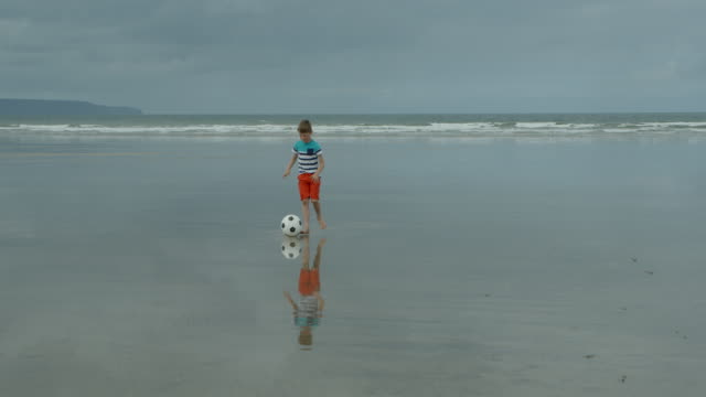 A young boy playing with his football on a beach. video