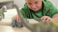 Young boy playing with toy dinosaurs video