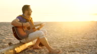 young boy plays guitar at sunset video
