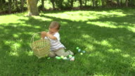 Young boy plays with Easter eggs video