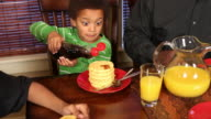 Young boy pouring syrup on waffles video