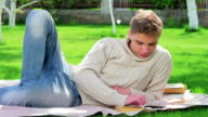 Young boy read book in the yard video