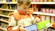 Young boy reading inscription on goods box in supermarket video