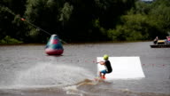A young boy rides on a wakeboard and jumping from a springboard video