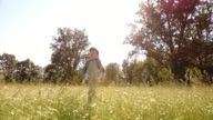 SLO MO DS Young boy running across high grass on a sunny day video