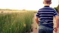 Young Boy Running at Sunset Through Tall Grass video