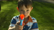 Young boy shooting toy gun at camera video