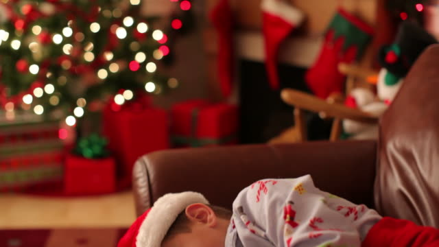 Young boy sleeps on couch Christmas eve video