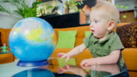 Young boy spinning the globe video