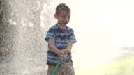 Young boy spraying hose video