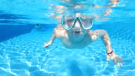 Young boy swimming underwater in a pool video