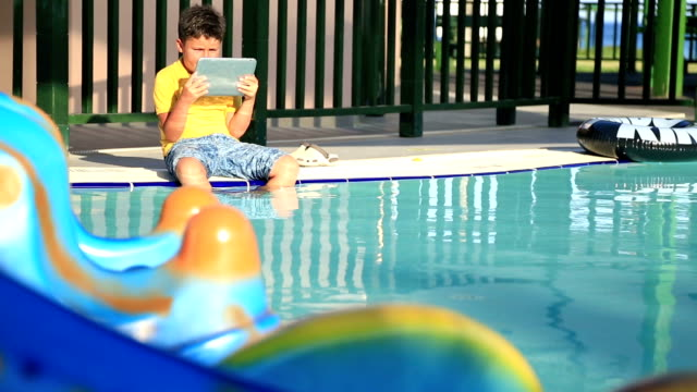 Young boy using digital tablet near the pool video